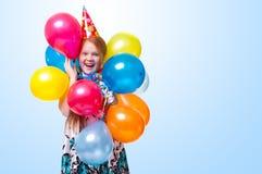 Fille heureuse avec des ballons sur le fond bleu Photographie stock libre de droits