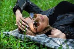 Fille heureuse avec des lunettes de soleil se trouvant sur une couverture dans l'herbe de pré le jour ensoleillé de ressort photos libres de droits