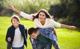 Fille heureuse avec deux garçons posant en parc de chute Images stock
