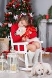 Fille heureuse avec deux golden retriever de chiots sur un fond d'arbre de Noël Photo libre de droits