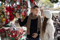 Fille heureuse avec l'ami choisissant la décoration de Noël Image libre de droits