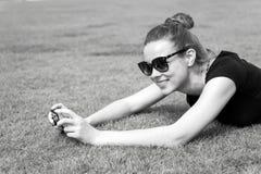 Fille heureuse avec l'appareil-photo sur l'herbe verte à Paris, France photos stock