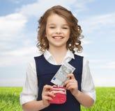 Fille heureuse avec la bourse et la monnaie fiduciaire Photo stock