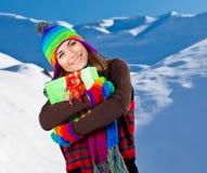 Fille heureuse avec le cadeau de Noël, verticale de l'hiver Photographie stock libre de droits