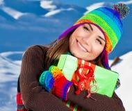 Fille heureuse avec le cadeau, verticale extérieure de l'hiver Photo libre de droits