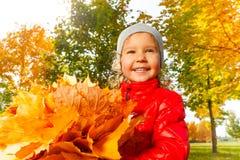 Fille heureuse avec le groupe de feuilles oranges lumineuses Photo stock