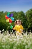 Fille heureuse avec le jouet de moulin à vent Image stock