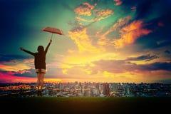 Fille heureuse avec le parapluie voyant le coucher du soleil au-dessus de la ville Photographie stock