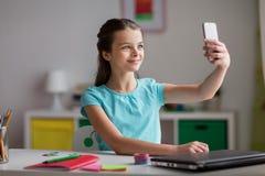 Fille heureuse avec le smartphone prenant le selfie à la maison Photo stock