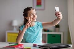 Fille heureuse avec le smartphone prenant le selfie à la maison Images libres de droits