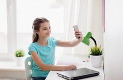 Fille heureuse avec le smartphone prenant le selfie à la maison Photographie stock