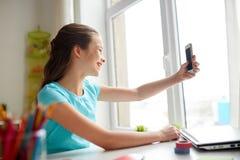 Fille heureuse avec le smartphone prenant le selfie à la maison Image stock
