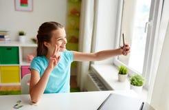 Fille heureuse avec le smartphone prenant le selfie à la maison Images stock