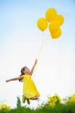 Fille heureuse avec les ballons jaunes Photographie stock