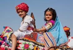 Fille heureuse avec un démon comme une commande de famille royale au festival de désert Image libre de droits