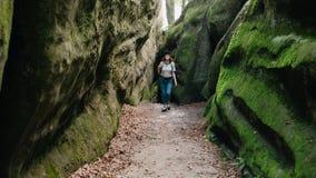 Fille heureuse avec un sac à dos marchant par les montagnes vertes et ayant l'amusement clips vidéos