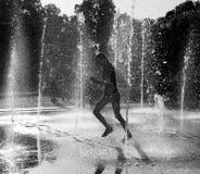 Fille heureuse ayant l'amusement entre les jets d'eau dans la fontaine Photographie stock libre de droits