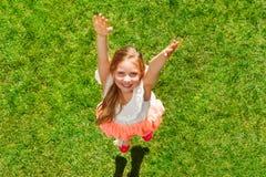 Fille heureuse ayant l'amusement sautant sur l'herbe verte Photo stock