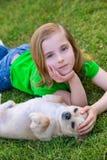 Fille heureuse blonde avec son portrait de chienchien de chiwawa Photographie stock libre de droits