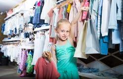 Fille heureuse chez la boutique de vêtements des enfants Images stock