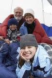 Fille heureuse détendant avec la famille dans la tente Photos libres de droits