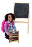 Fille heureuse d'école avec l'abaque et le sac à dos rose Images libres de droits