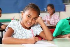 Fille heureuse d'école avec le beau sourire dans la classe Image stock