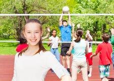 Fille heureuse d'adolescent avec l'équipe jouant le volleyball Photos libres de droits