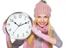 Fille heureuse d'adolescent dans le chapeau et l'écharpe d'hiver montrant l'horloge Photographie stock