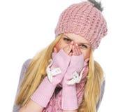 Fille heureuse d'adolescent dans le visage fermant de chapeau et d'écharpe d'hiver Photos libres de droits