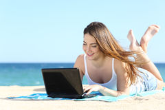 Fille heureuse d'adolescent passant en revue le media social dans un ordinateur portable sur la plage Image stock