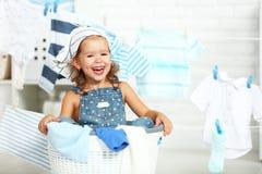 Fille heureuse d'amusement d'enfant petite pour laver des vêtements et des rires dans le laund photos stock