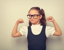 Fille heureuse d'amusement dans des lunettes montrant ses bras de muscle à l'école u images stock