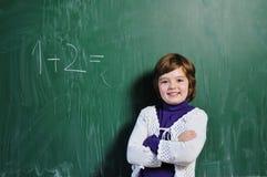 Fille heureuse d'école sur des classes de maths Photographie stock libre de droits