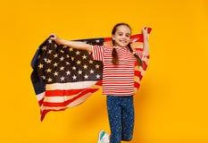 Fille heureuse d'enfant avec le drapeau des Etats-Unis d'Amérique Etats-Unis sur le fond jaune photo stock