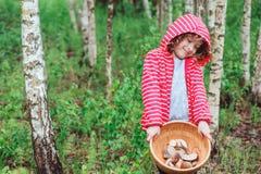 Fille heureuse d'enfant avec les champignons sauvages comestibles sauvages du plat en bois Image libre de droits