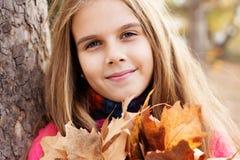 Fille heureuse d'enfant avec les feuilles d'or tombées Photo libre de droits