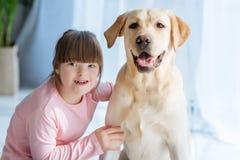 Fille heureuse d'enfant avec syndrome de Down aimant Labrador images stock