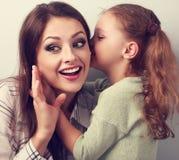 Fille heureuse d'enfant chuchotant le secret à sa mère étonnante dedans Photos stock