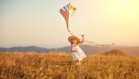 Fille heureuse d'enfant courant avec le cerf-volant au coucher du soleil dehors Images libres de droits