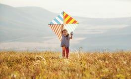 Fille heureuse d'enfant courant avec le cerf-volant au coucher du soleil dehors Image stock