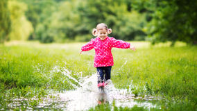 Fille heureuse d'enfant courant et sautant dans les magmas après pluie Photos stock