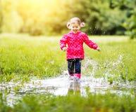 Fille heureuse d'enfant courant et sautant dans les magmas après pluie Photographie stock