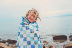 Fille heureuse d'enfant couverte dans la couverture d'édredon, vacances d'été confortables sur le bord de la mer Photographie stock