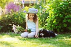 Fille heureuse d'enfant détendant dans le jardin d'été avec son chien d'épagneul, chapeau de port de jardinier et tenant le bouqu image libre de droits