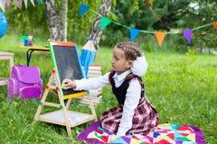 Fille heureuse d'enfant d'enfant d'écolière s'asseyant sur l'herbe et écrivant dessus Photographie stock