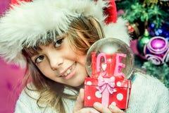 Fille heureuse d'enfant dans un chapeau de Noël tenant le cadeau en verre de globe de Photographie stock