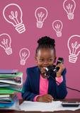 Fille heureuse d'enfant de bureau parlant au téléphone sur le fond rose avec des icônes d'ampoules Photo stock