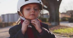 Fille heureuse d'enfant de fille mettant sur le casque de sécurité avant de monter la bicyclette dans le parc de ville Enfance, c banque de vidéos