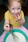 Fille heureuse d'enfant en bas âge léchant la pâte lisse. Photo stock